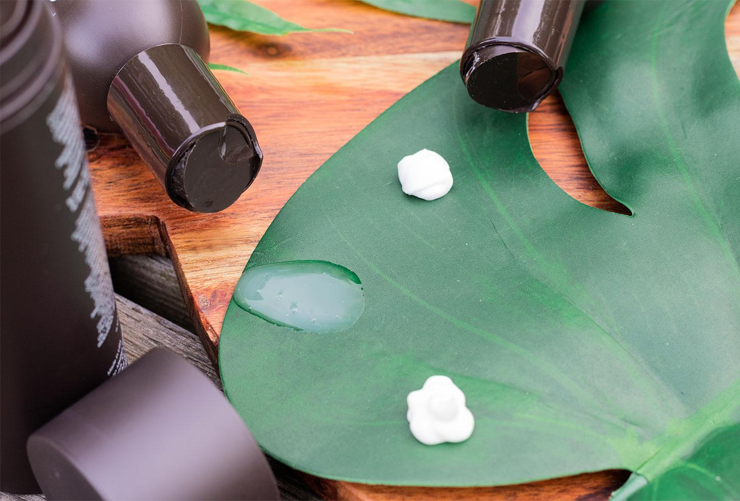 Zoom sur la texture des 3 produits pour cheveux abîmés de John Masters Organics sur une feuille de bananier