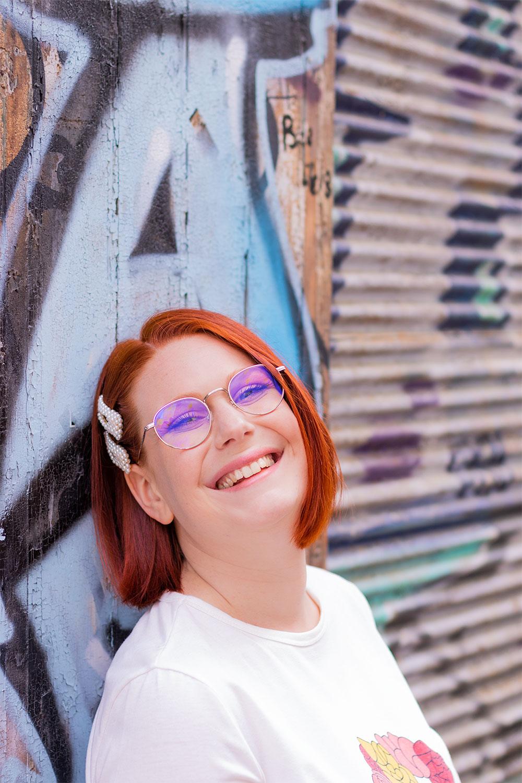 Appuyée le long d'un mur tagué, de profil avec le sourire, des barrettes en perles sur le côté droit des cheveux
