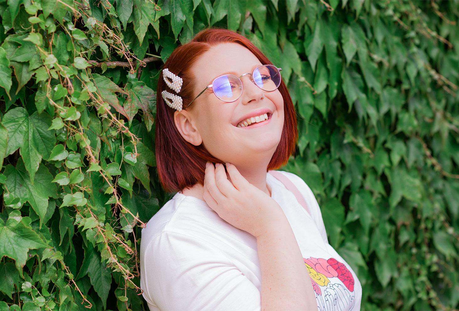Zoom sur les barrettes en perles blanches SheIn portée, de profil le long d'un mur recouvert de feuilles, avec le sourire