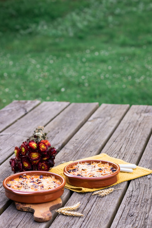 Les clafoutis salés aubergine et chorizo posé sur une table de pique-nique en bois avec un bouquet de fleurs séchées rouges et oranges
