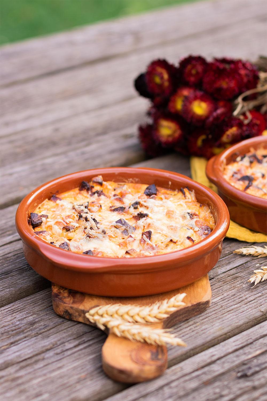 Zoom sur le clafoutis salé aubergine et chorizo dans un plat en terre cuite, posé sur une planche à découper en bois avec des épis de blé séchés