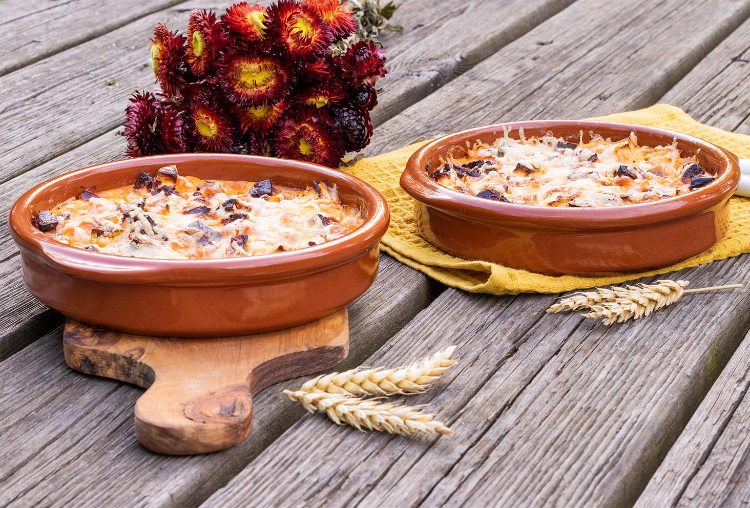 Les clafoutis salés aubergine et chorizo posé sur un torchon jaune moutarde et sur une planche à découper, sur une table en bois au milieu d'épis de blé et de fleurs séchées
