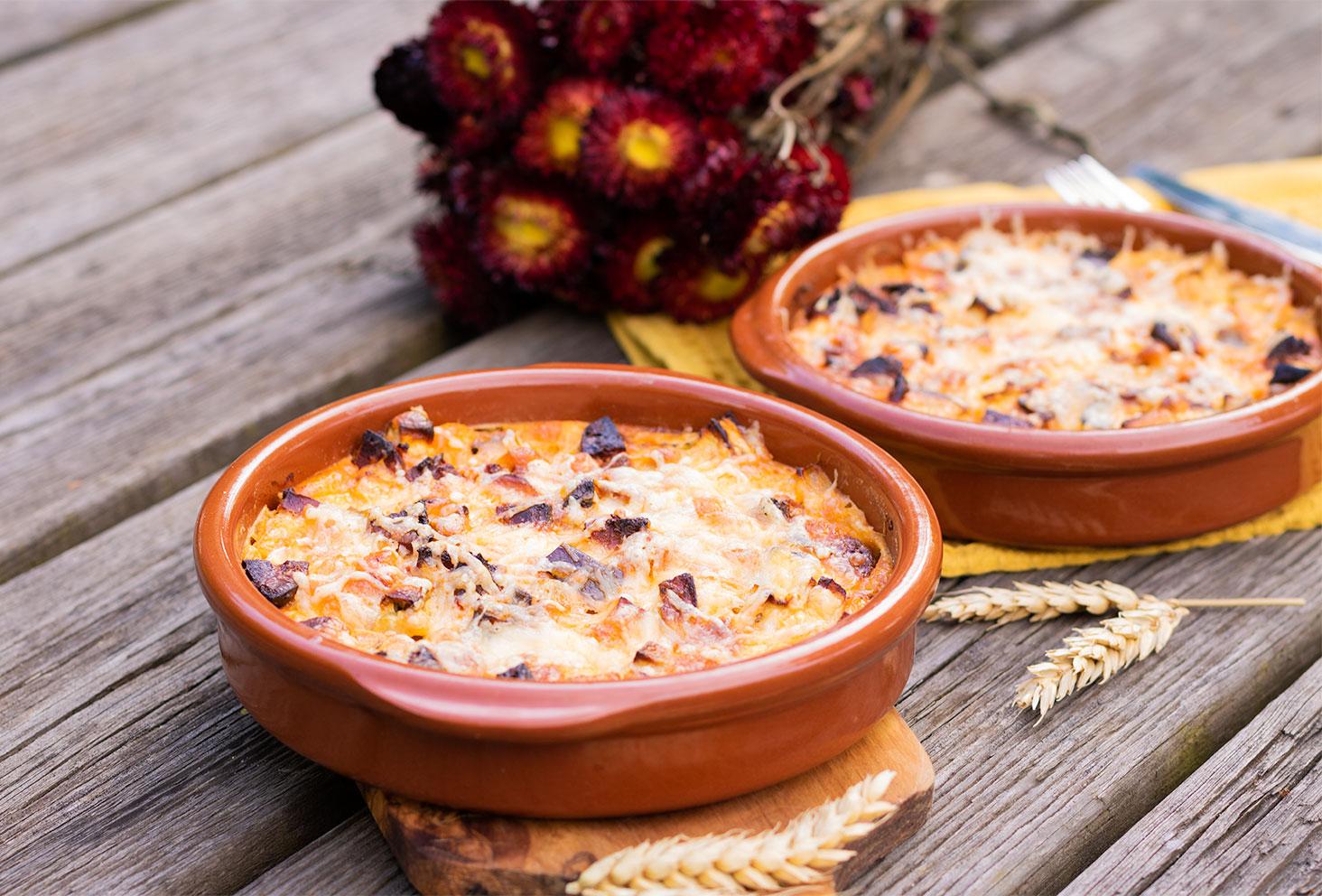 Clafoutis salé aubergine et chorizo posé sur une table en bois au milieu de diverses fleurs séchées