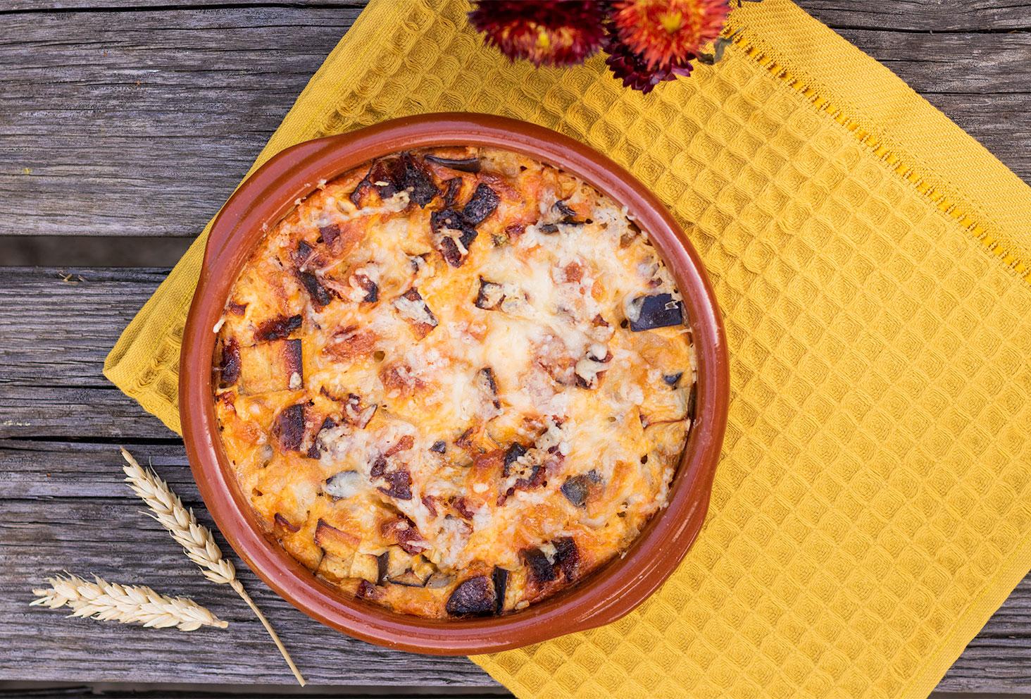 Zoom sur la texture du clafoutis salé aubergine, chorizo et mozzarella, dans un plat en terre cuite, posé sur un torchon jaune moutarde