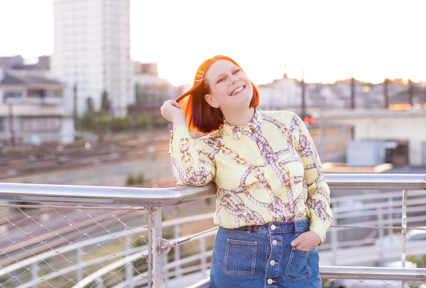 Au coucher du soleil sur la passerelle avec vue sur les rails du train de la gare de Tours, avec le sourire une main dans les cheveux et l'autre dans une poche de la jupe en jean Zara portée
