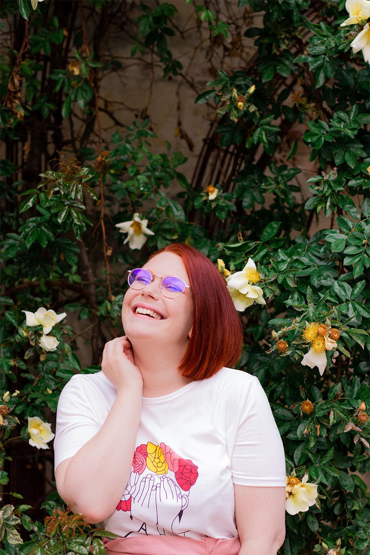 Dans la rue devant un buisson de fleurs jaunes, avec le sourire une main dans le cou, pour montrer le t-shirt à motifs femmes et couronne fleurie de Shein