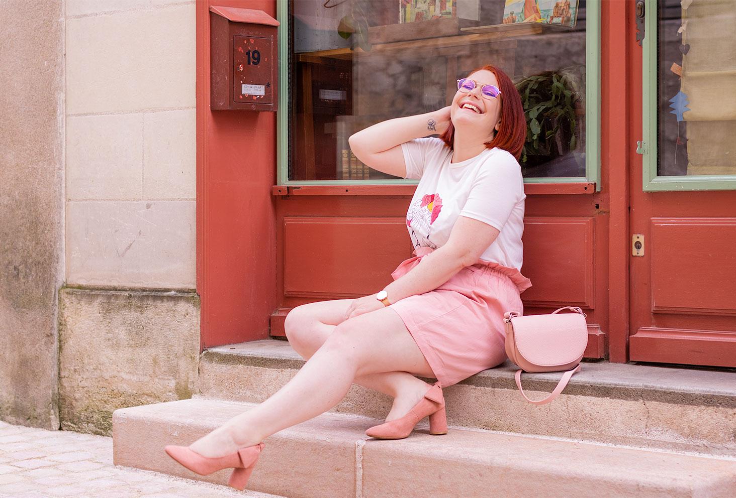 Assise dans les marches devant une boutique à la façade couleur brique, en jupe et escarpins roses, une main dans les cheveux