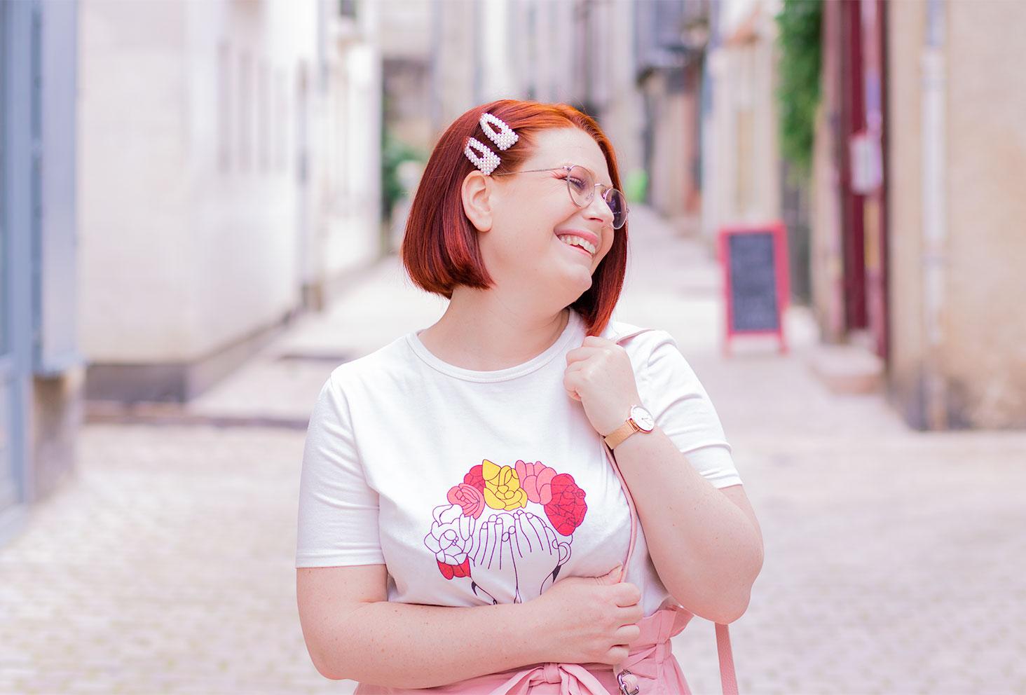 Dans la rue de face avec le visage de profil, des barrettes en perles dans les cheveux avec le sourire, les mains accrochées à la bandoulière du sac sur l'épaule