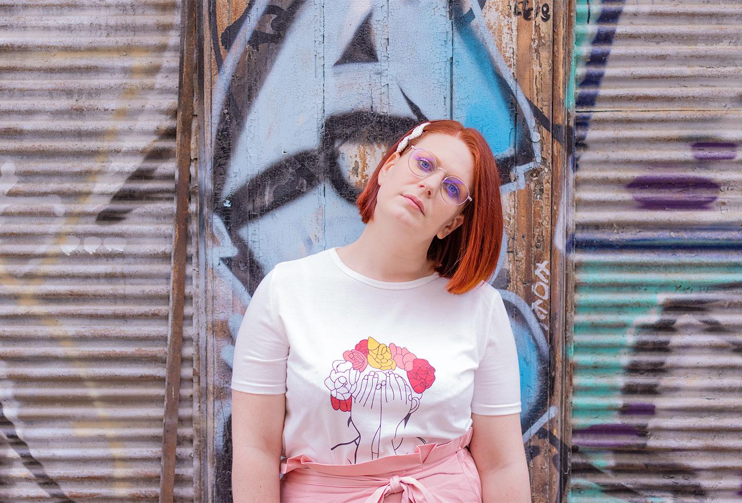Dans la rue devant un graffiti sans le sourire, les mains le long du corps en t-shirt Shein