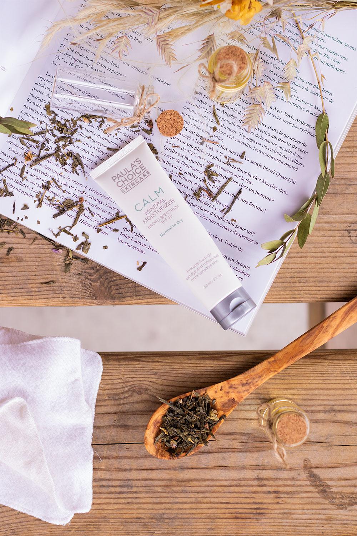 Flatlay de la crème de jour de Paula's Choice posée sur un magazine ouvert sur une table en bois, au milieu de feuilles de thé et d'une cuillère en bois remplie de thé vert