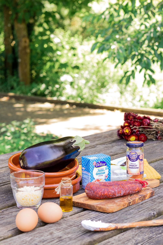 Les ingrédients de la recette du clafoutis salé aubergine et chorizo, sur une table de pique-nique en bois