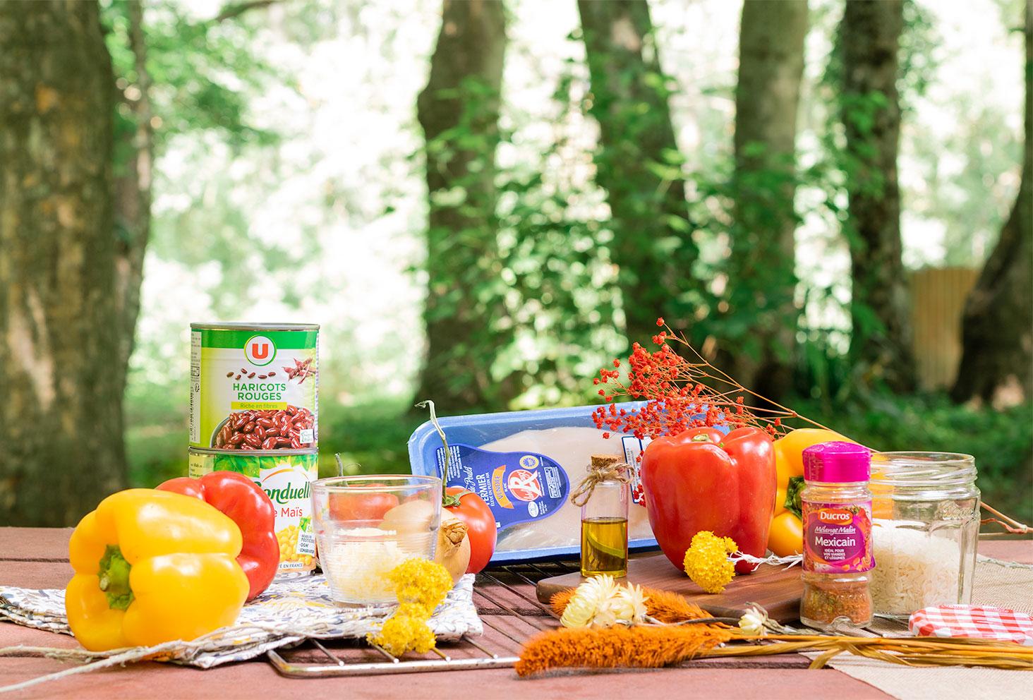 Les ingrédients nécessaires à la réalisation de la recette de poivrons farcis à la mexicaine pour l'été, sur une table de pique-nique en forêt