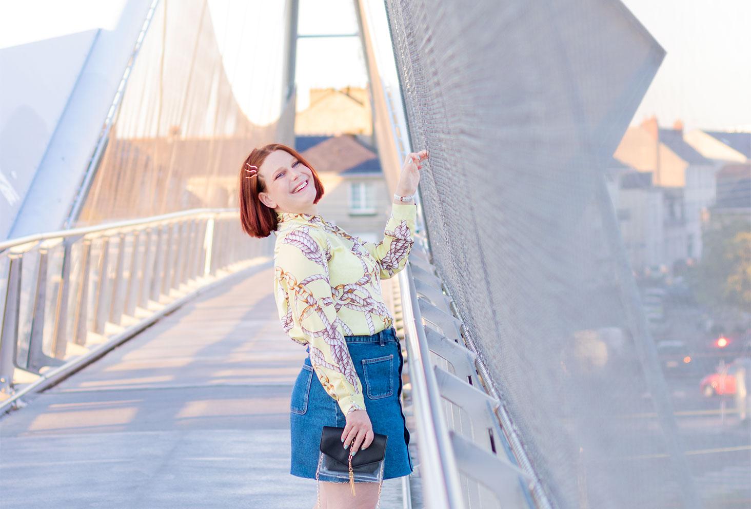 De profil accrochée au grillage d'une passerelle street, de profil avec le sourire, en jupe et chemise une pochette transparente dans la main