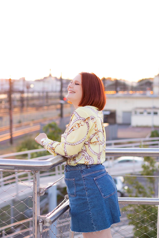 De dos au coucher du soleil de la gare de Tours, en jupe en jeans avec une chemise jaune rentrée à l'intérieur, accoudée à la rambarde d'une passerelle en métal