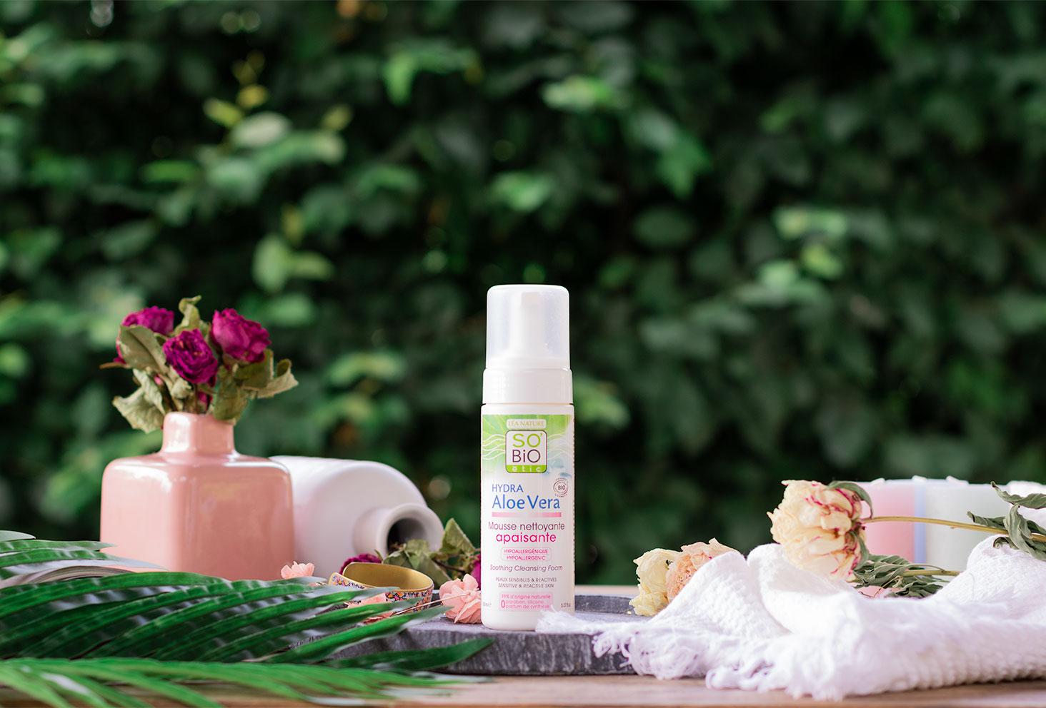 La mousse nettoyante apaisante de SO'BiO étic sur une table en bois au milieu d'une déco de salle de bain au milieu de fleurs séchées