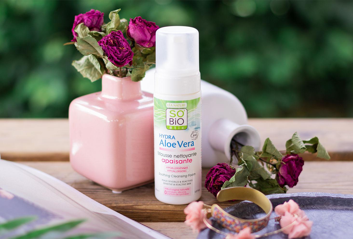 La mousse nettoyante apaisante SO'BiO étic sur une table en bois, debout devant des vases remplis de fleurs séchées violettes