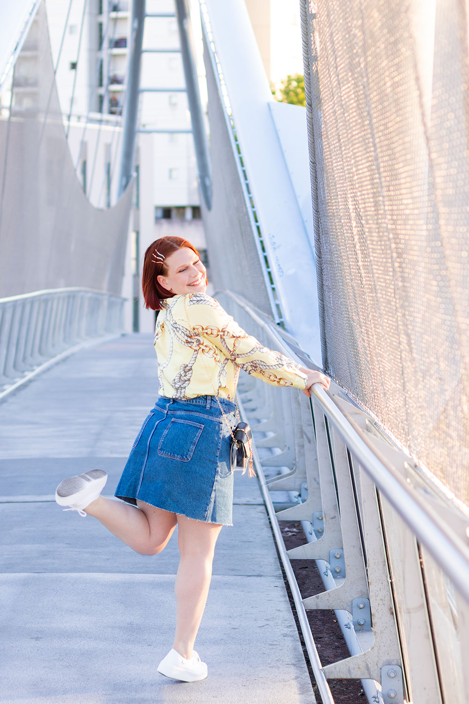 En jupe en jean et chemise, appuyée sur une rambarde en métal, la jambe levée avec le sourire