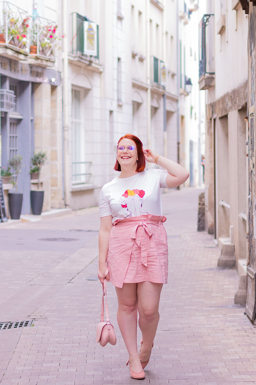 Dans la rue en look tout rose, en train de marcher un sac à la main et l'autre dans les cheveux