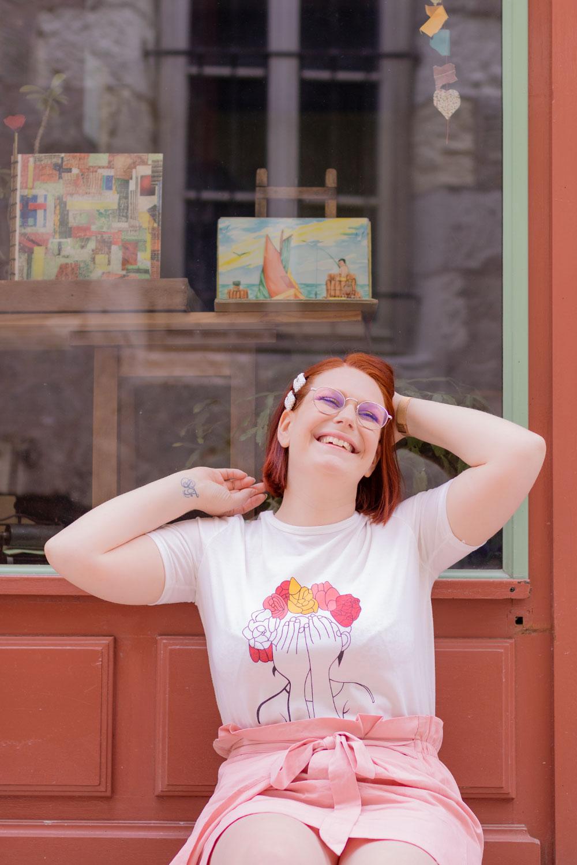 Assise le long de la façade d'une boutique couleur brique, avec le sourire les mains levées dans les cheveux