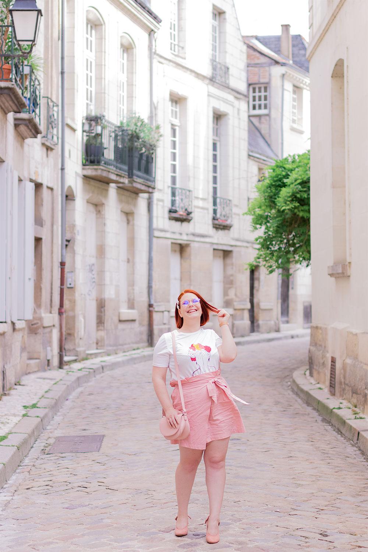 En train de marché dans la rue en jupe rose poudrée, une main dans les cheveux et l'autre posée sur le sac en bandoulière