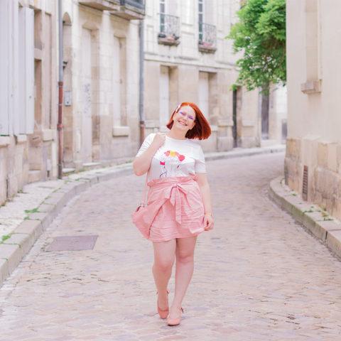En train de marcher au milieu d'une rue pavé en look entièrement rose poudré