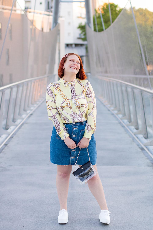 Look chemise et jupe en jeans, avec le sourire et des barrettes dorées dans les cheveux, au milieu d'une passerelle à Tours