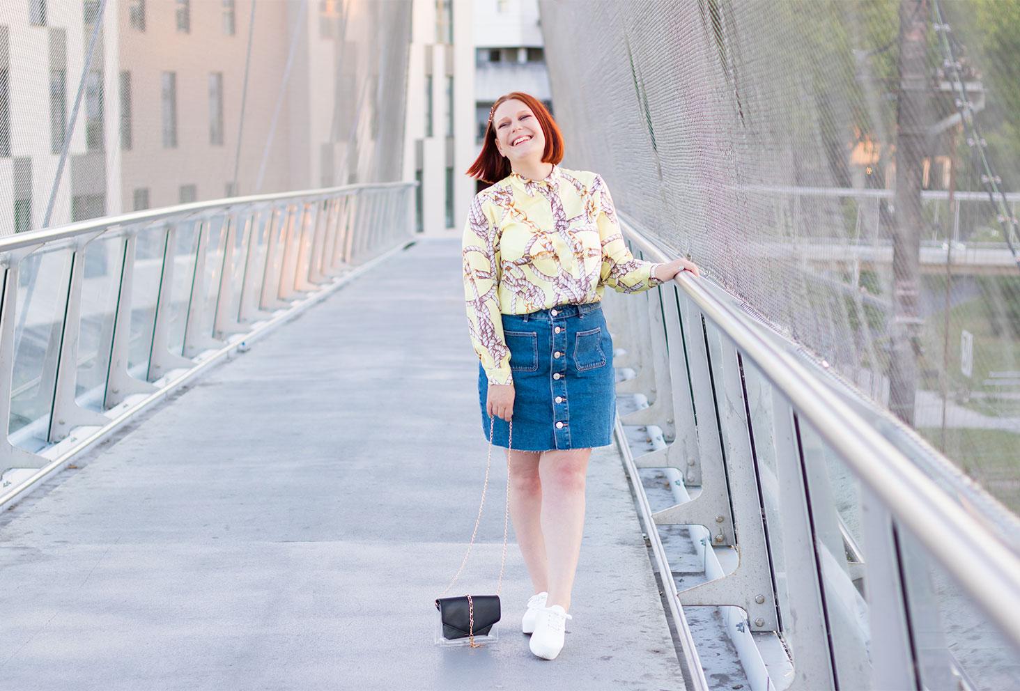 Appuyée à la rambarde en métal d'une passerelle street, en jupe en jean avec une chemise fluide jaune Zara