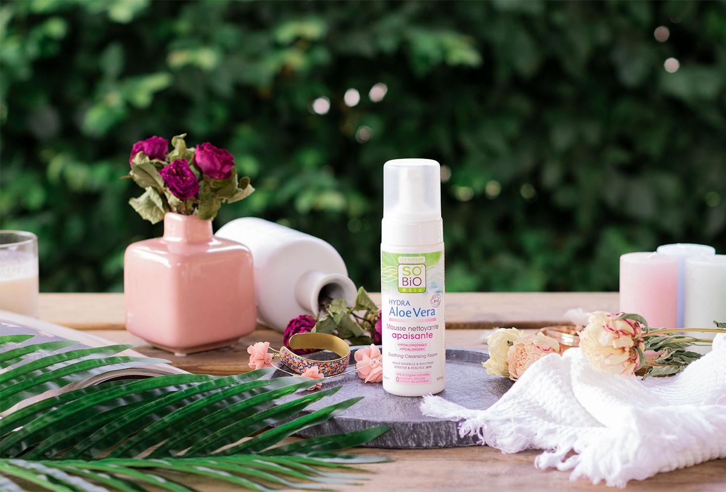 La mousse nettoyante apaisante de SO'BiO étic posé sur une plaque d'ardoise sur une table en bois, au milieu d'un décor de salle de bain, fleurs séchées et bougies vertes et roses