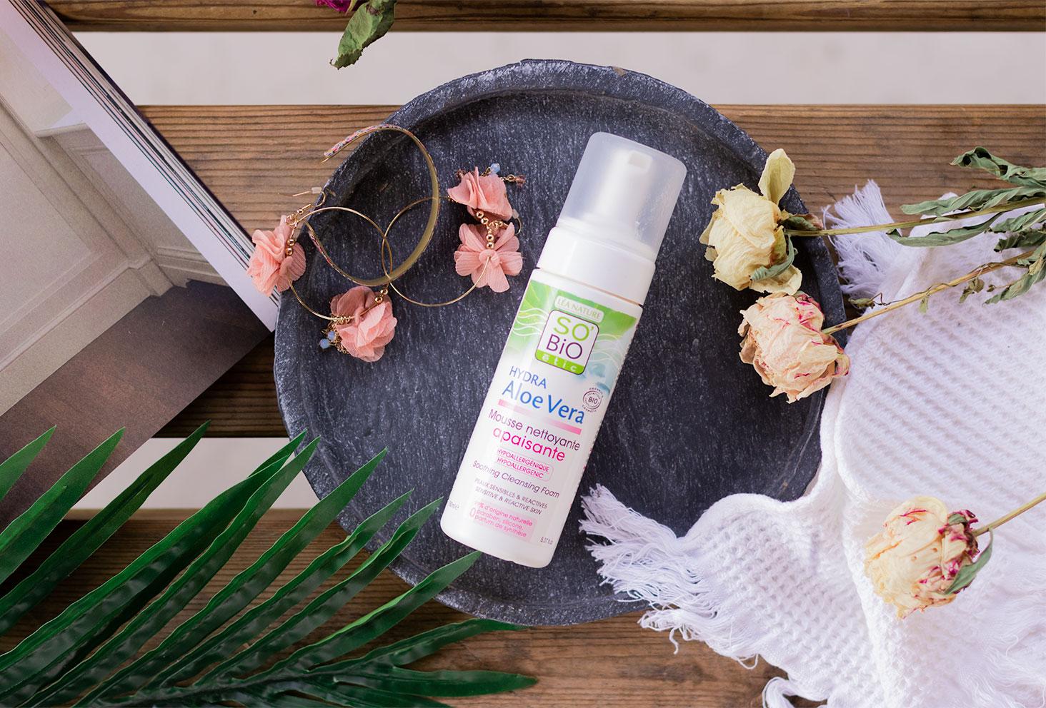 Vu de haut, la mousse nettoyante apaisante SO'BiO étic posée sur une plaque de marbre, sur une table en bois à côté d'un magazine, de fleurs séchées et d'une serviette blanche