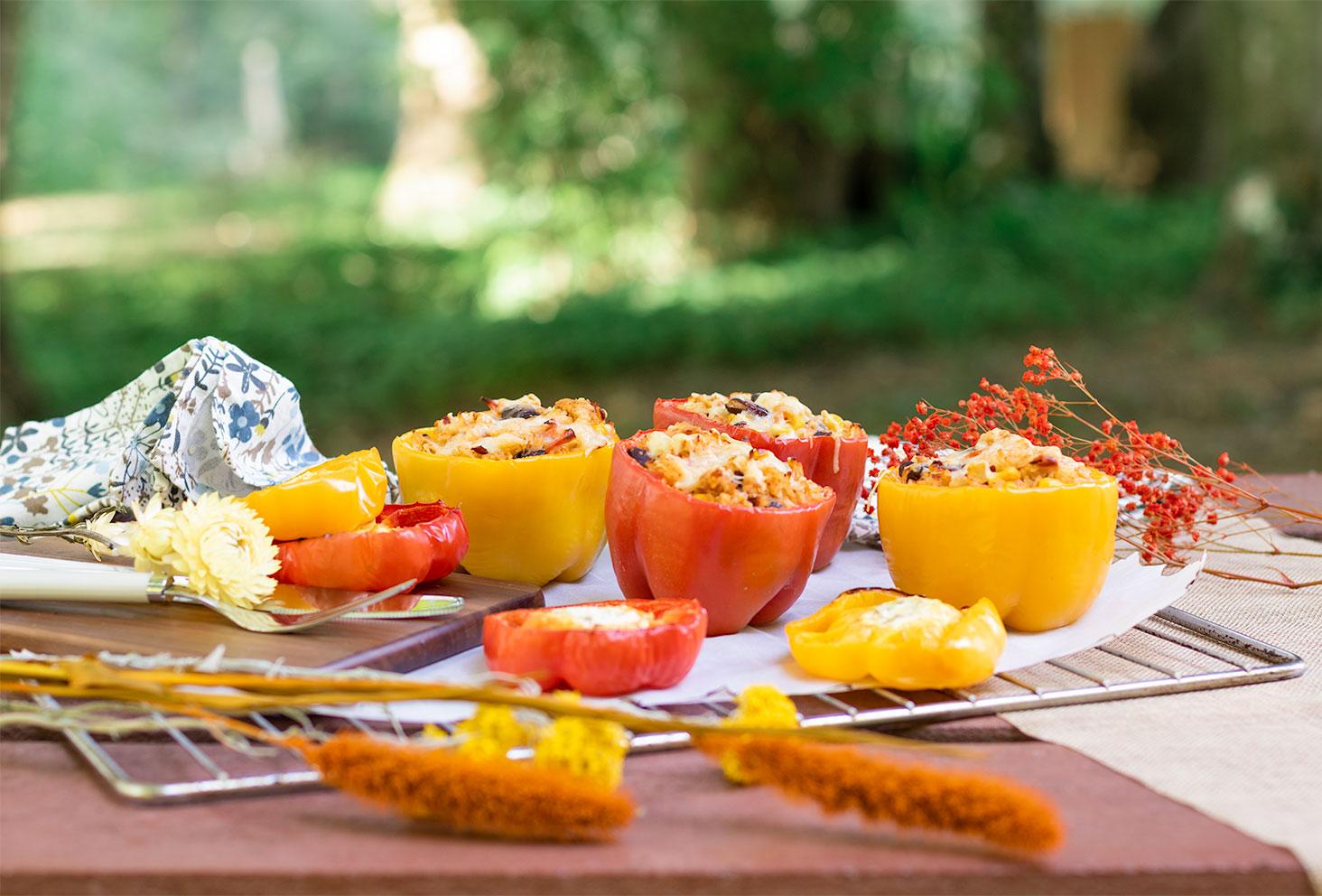 La recette de poivrons farcis facile, posés sur une plaque de four avec des couverts et des fleurs séchées, sur une table extérieure