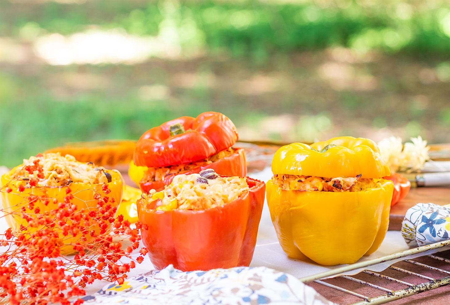 Zoom sur des poivrons jaunes et rouges farcis, avec ou sans leurs chapeaux, sur une grille de four posée dehors sur une table