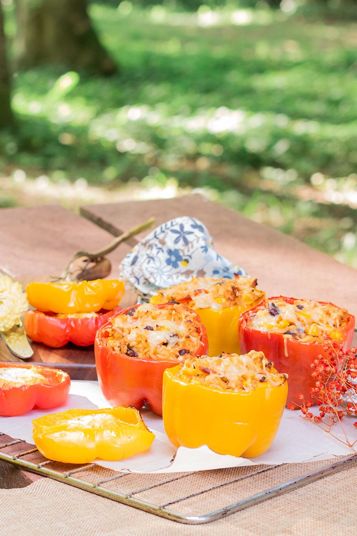 Poivrons farcis à la mexicaine pour l'été, posés sur la grille du four sur une table de pique-nique au milieu des bois
