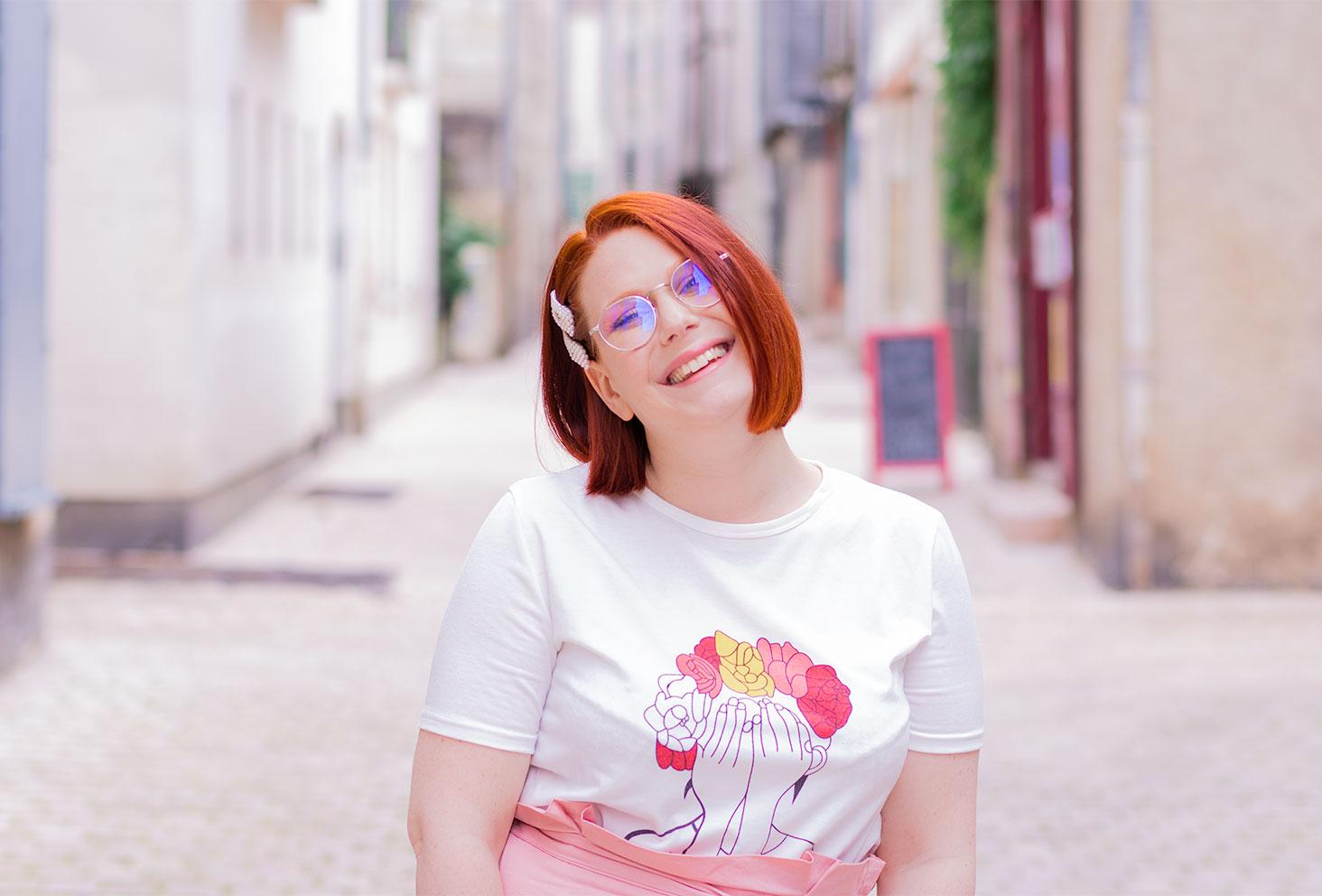 Dans la rue de face, portrait avec le sourire et des barrettes perlées dans les cheveux, en t-shirt blanc à grosses fleurs roses Shein