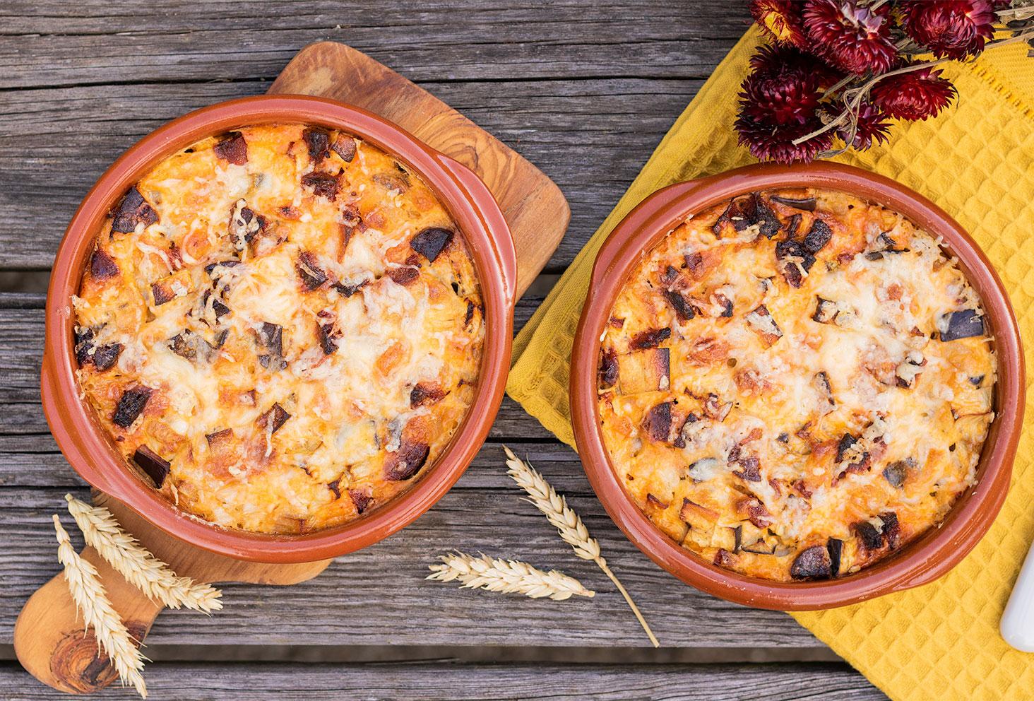 La recette du clafoutis salé aubergine chorizo, dans des ramequins en terre cuite sur une table en bois au milieu d'épis de blé