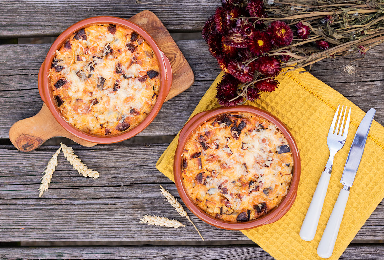 Recette du clafoutis salé aubergine et chorizo, dans des plats en terre cuite, sur une table en bois au milieu de fleurs séchées