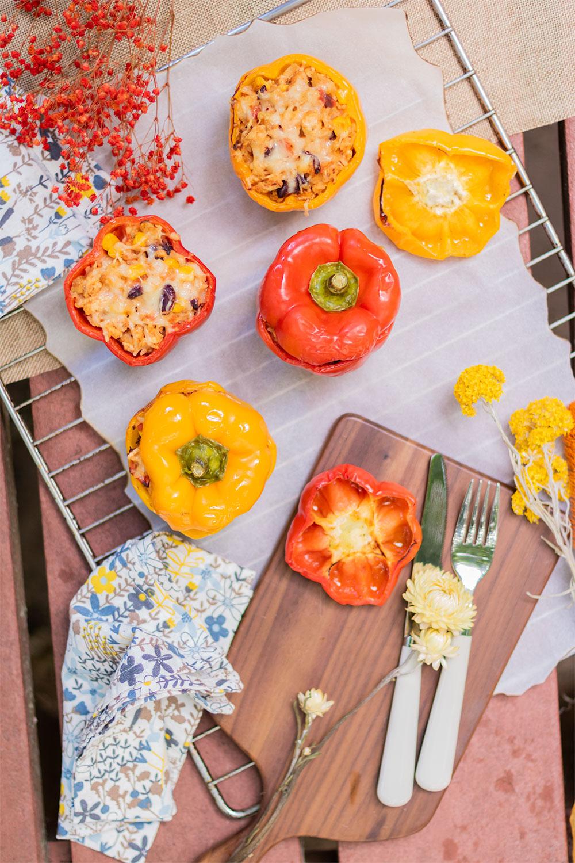 Recette facile de poivrons farcis vu de haut, sur une grille de four sur laquelle se trouve également une planche à découper, des couverts, des serviettes fleuries et des fleurs séchées