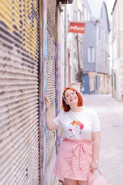 Dans la rue le long d'un rideau de fer tagué, en look rose poudré avec le sourire