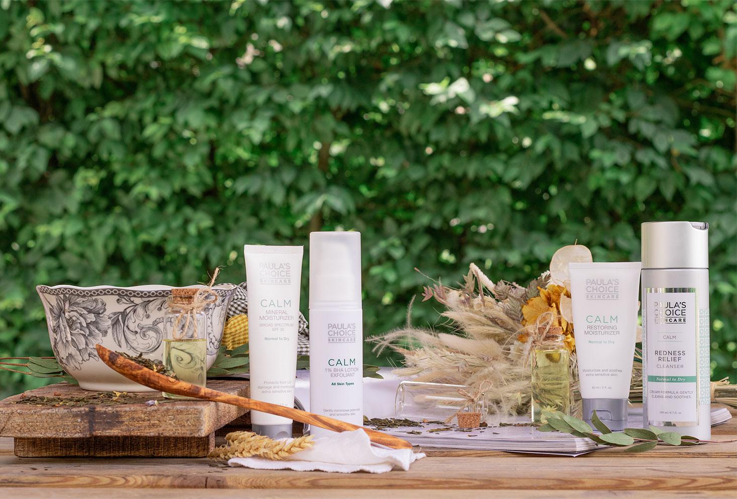 La gamma de produits CALM de Paula's Choice sur une table en bois au milieu de fleurs séchées