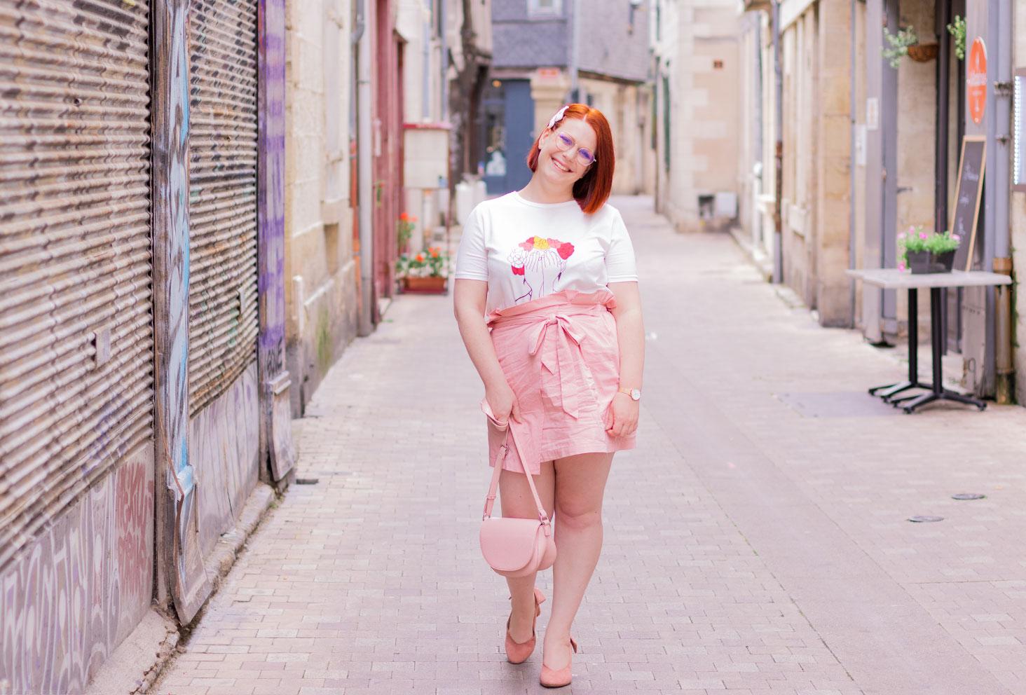 Dans la rue en train de marcher avec le sourire, en look entièrement rose, le sac en bandoulière tenu à la main