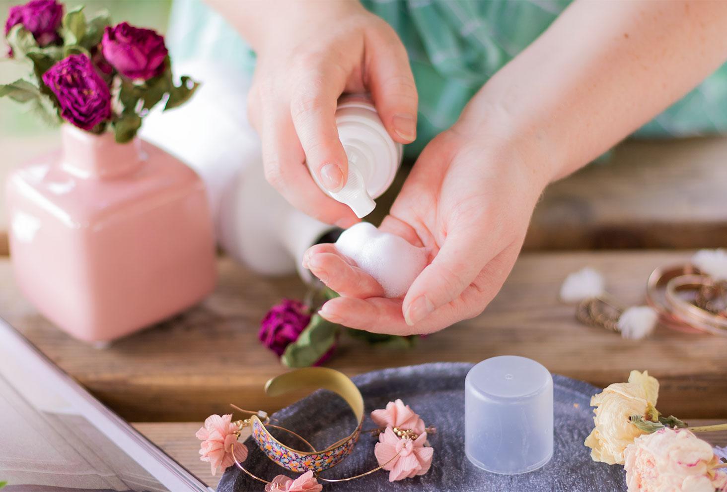 Zoom sur la texture mousse blanche dans le creux de la main de la mousse nettoyante apaisante SO'BiO étic, au dessus d'une table en bois