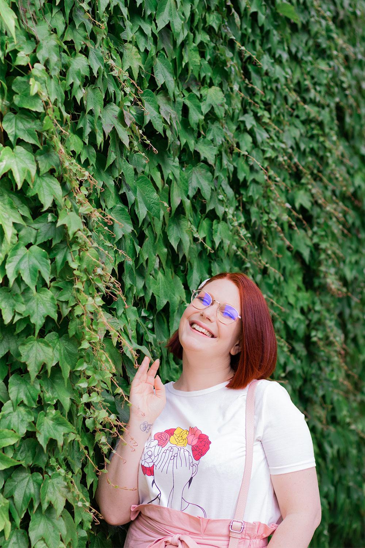 Appuyé le long d'un mur recouvert de feuilles vertes, en t-shirt blanc à motif femme Shein, avec le sourire