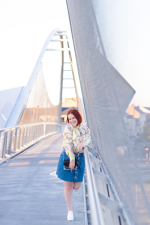 Sur une passerelle street au-dessus des rails du train, en jupe en jean et chemise fluide jaune, une jambe en l'air appuyée contre la rambarde