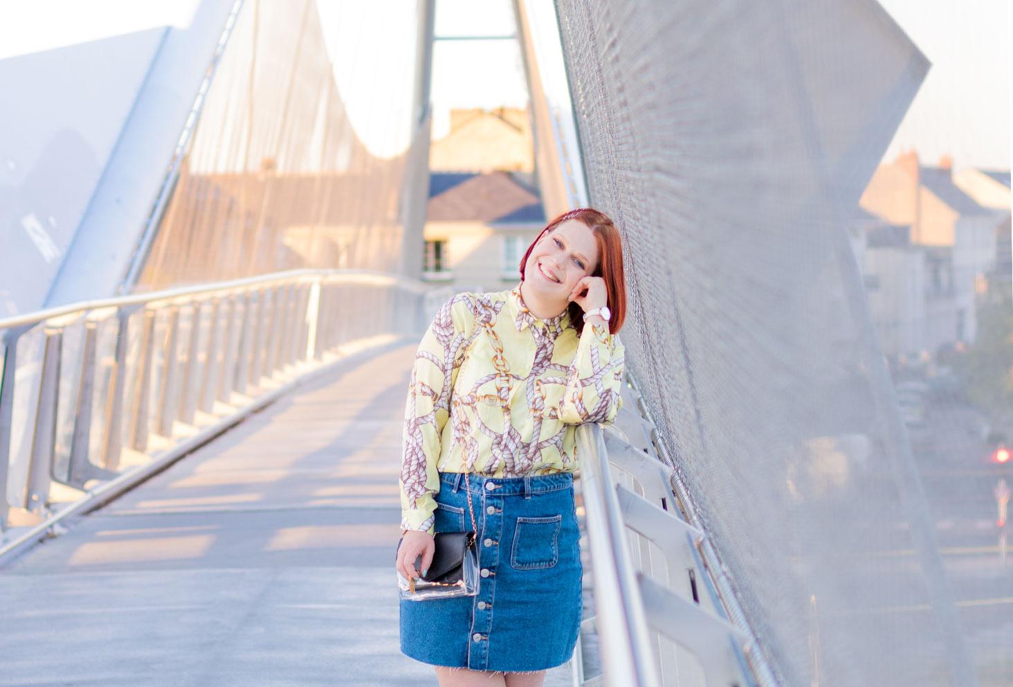 Accoudée au rebord en métal de la passerelle street de la gare de Tours, en jupe en jean à boutons et chemise jaune fluide