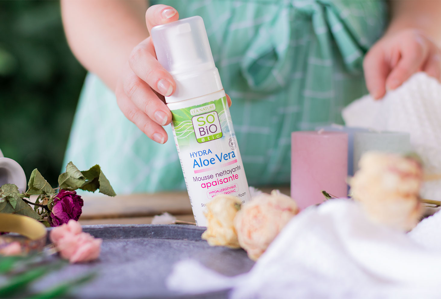 Dans la main, la mousse nettoyante apaisante SO'BiO étic et dans l'autre main, une serviette blanche, dans un décor de salle de bain