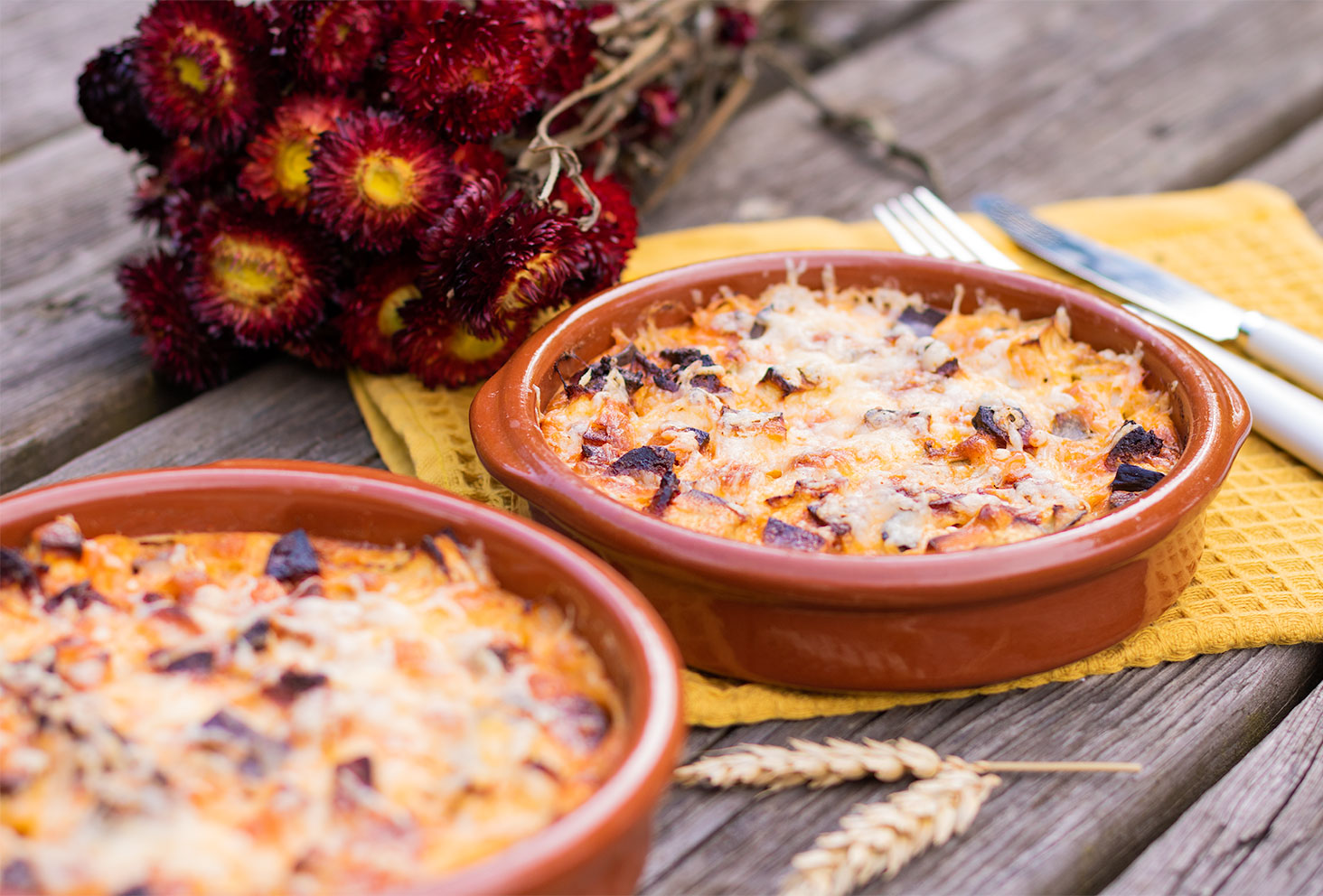 Zoom sur le clafoutis salé chorizo et aubergine dans un plat en terre cuite pour l'été posé sur une table en bois de pique-nique à côté d'un bouquet de fleurs séchées