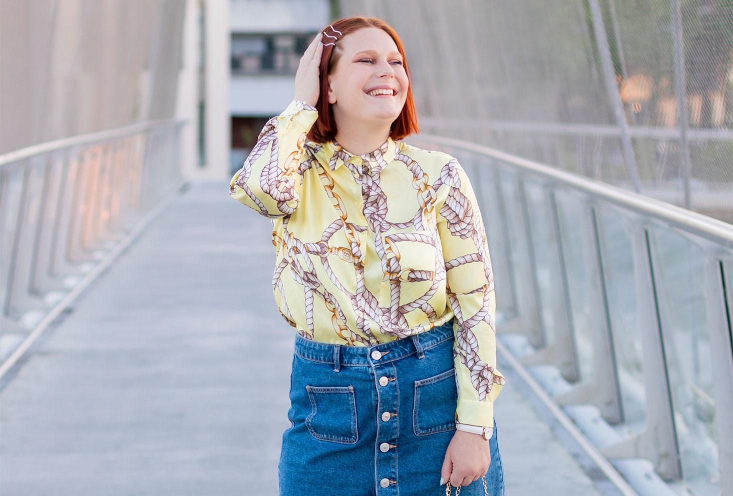 Zoom sur la chemise jaune à motifs de nœuds Zara portée rentrée dans une jupe en jeans à boutons, une main dans les cheveux au milieu d'une passerelle en métal à la gare de Tours