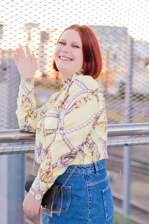 De profil contre le rebord de la passerelle street de la gare de Tours, en chemise fluide jaune rentrée dans une jupe en denim, avec le sourire