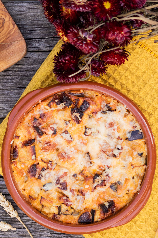 Zoom sur une recette de l'été, le clafoutis salé aubergine et chorizo, posé sur un torchon jaune au milieu de fleurs séchées