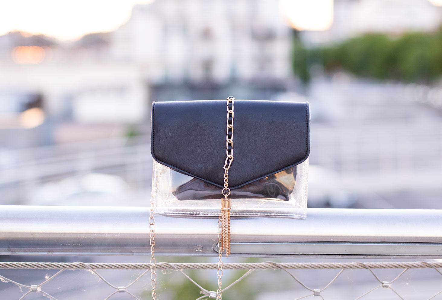 Zoom sur la pochette transparente, noire et doré de Shein posé sur la rambarde en métal d'une passerelle style street