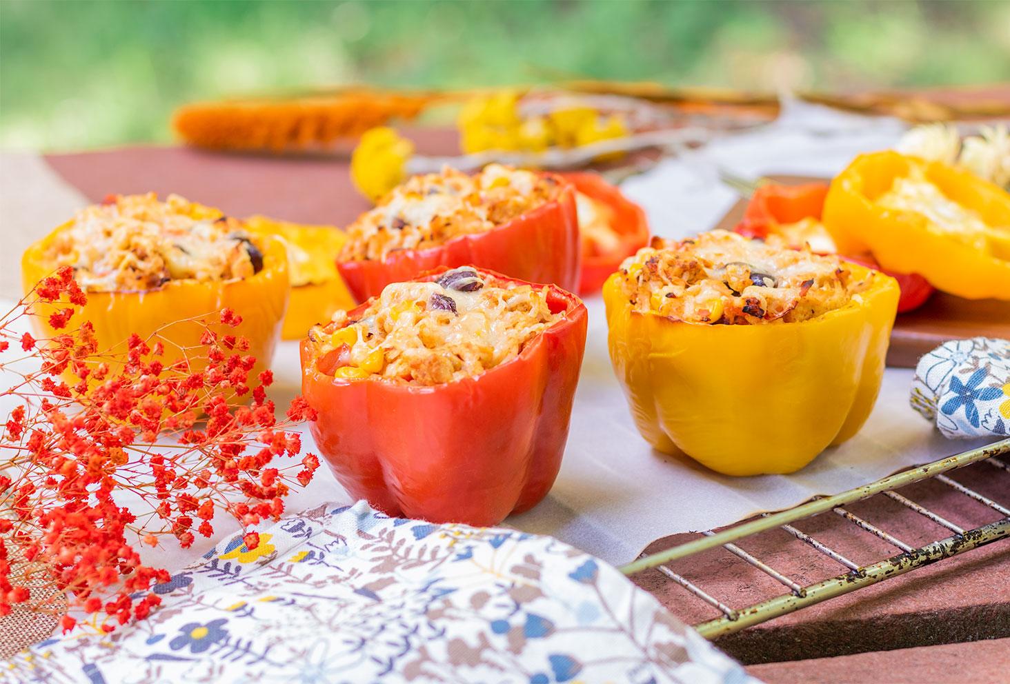 Zoom sur des poivrons farcis à la mexicaine pour l'été, sur une grille de four au milieu de fleurs séchées